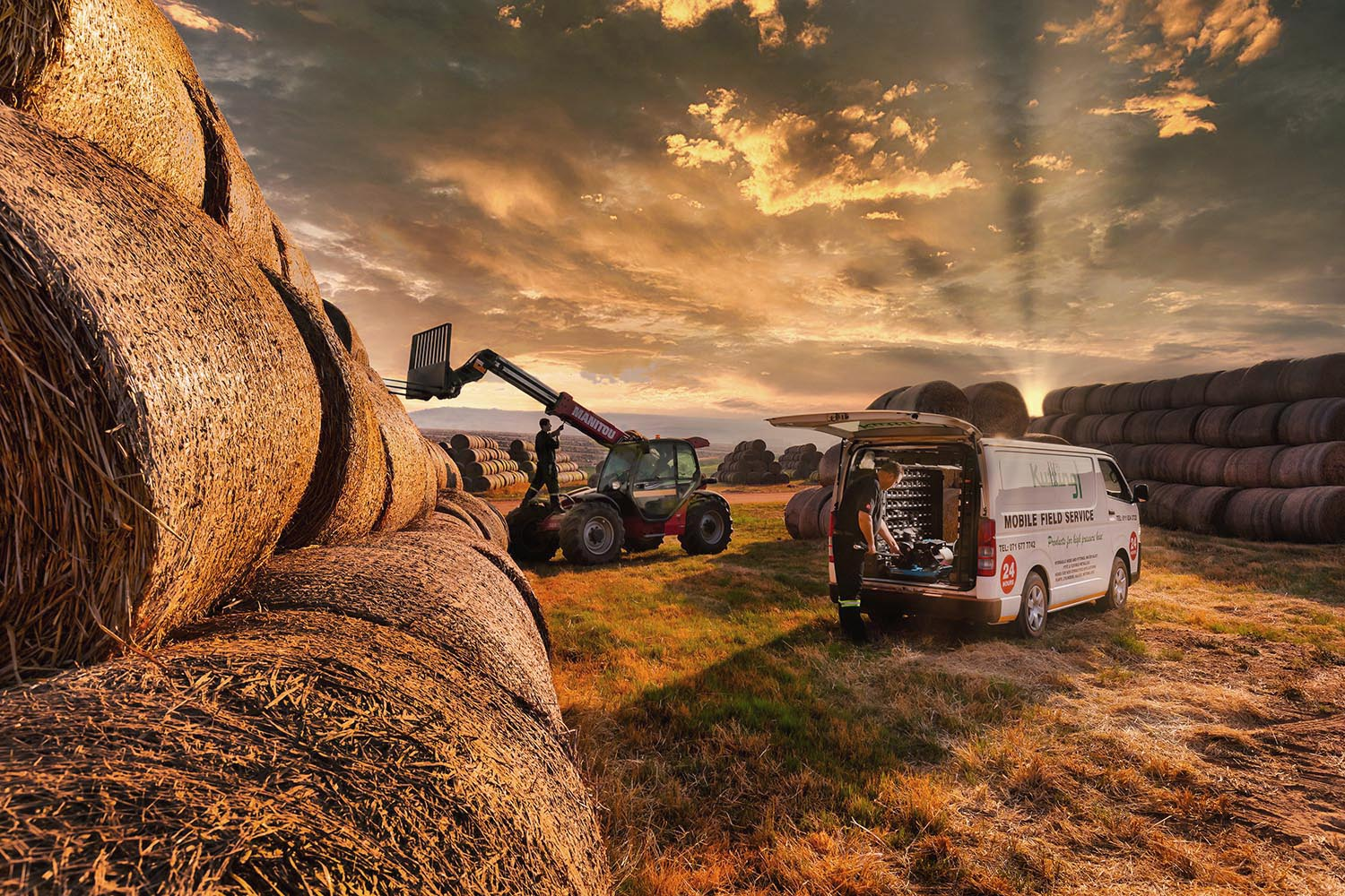 Agricultural equipment being maintained on a farm at sunset