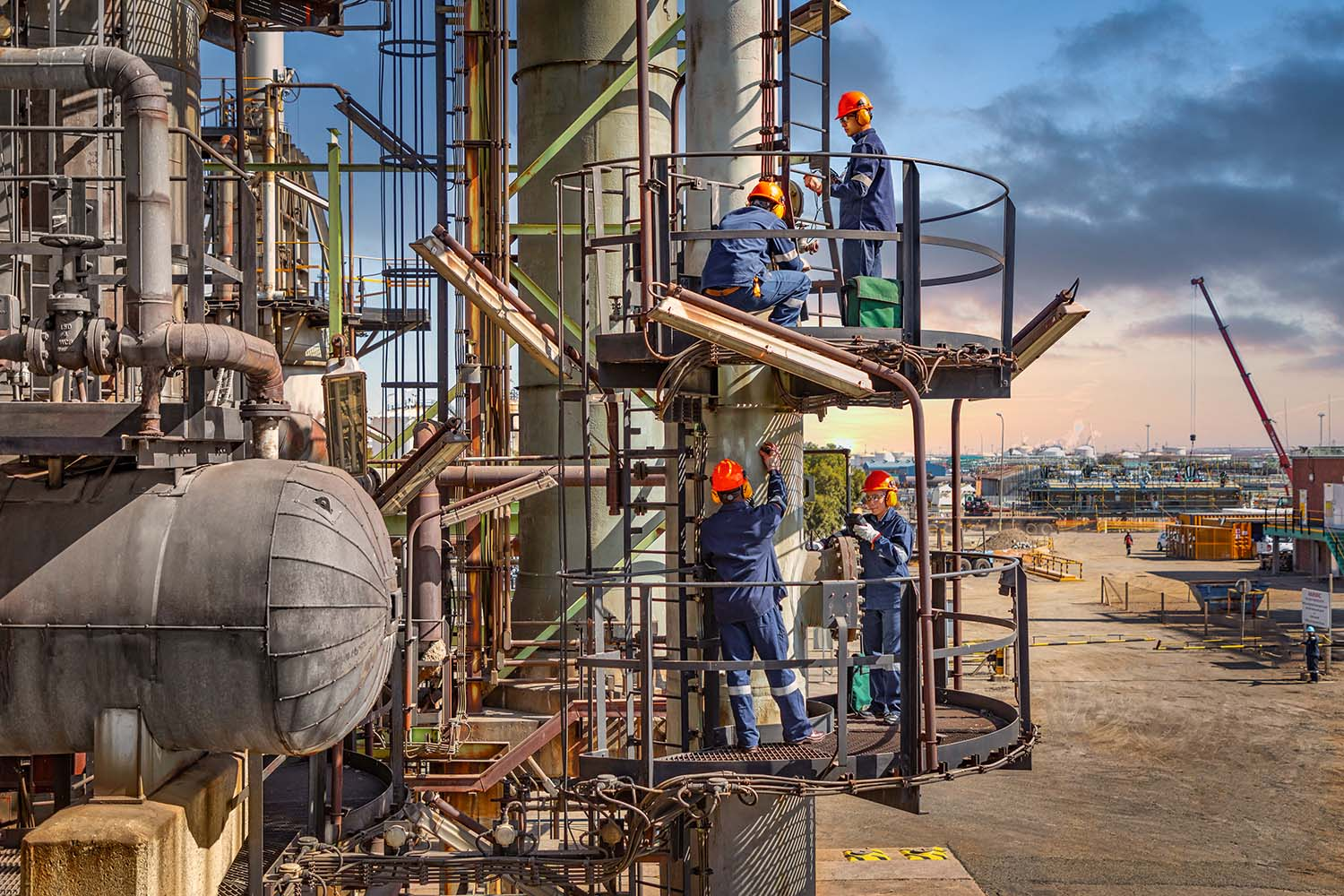 Four technicians inspecting chemical plant