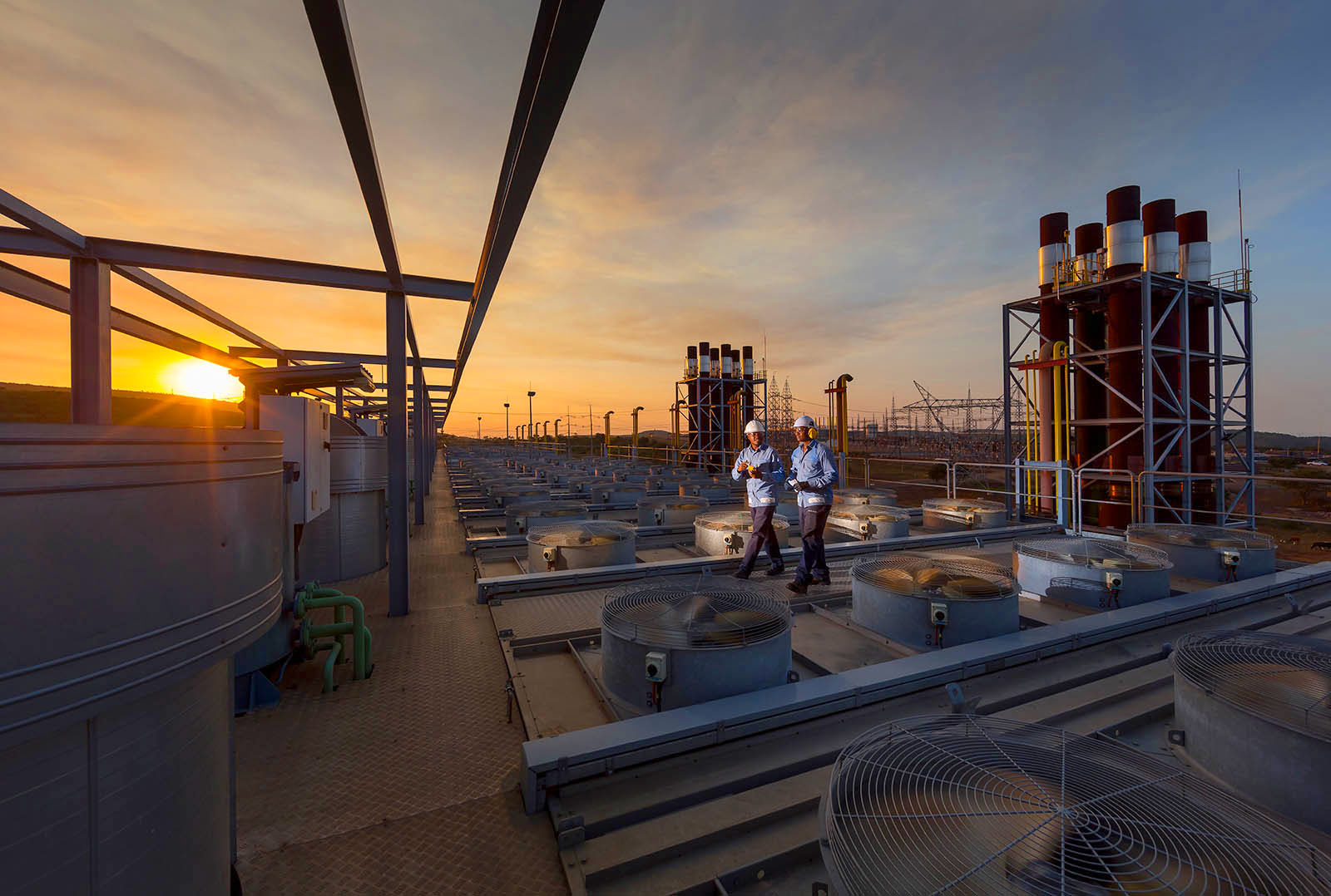 Sunset two technicians discus progress on industrial gas engine power plant